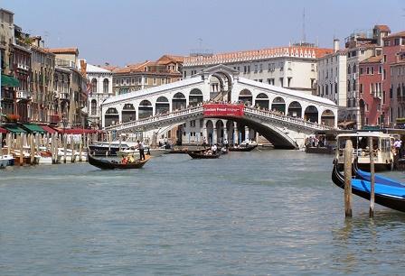 The Rialto Bridge is crossing the Grand Canal